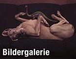 Polaroid-Foto von William Wegman: Hund liegt auf dem Rücken auf einer Couch, eine Dinosaurier-Spielfigur auf seinem Bauch