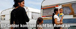 Romafrauen und -kinder vor Wohnwägen