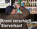 Ein Mann trinkt vor einem Getränkekiosk aus einer Flasche.