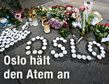 Blumen und Kerzen liegen auf einem Gehsteig in Oslo