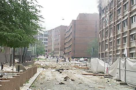 Trümmer liegen auf der Straße vor einem zerstörten Gebäude