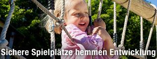 Kleines Mädchen auf einem Klettergerüst