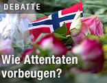 Eine kleine norwegische Fahne liegt zwischen Blumen