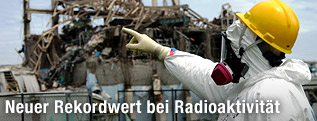 Mann in Strahlenschutzanzug vor Reaktor 3 des AKW Fukushima