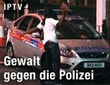 Vermummter schlägt mit einem Stein auf die Windschutzscheibe eines Polizeiautos ein
