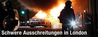 Polizist steht vor einem brennenden Fahrzeug