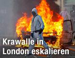 Maskierter Mann vor brennendem Auto in London