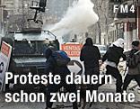 Demonstranten werfen Gegenstände gegen ein gepanzertes Fahrzeug