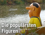Eine lebensgroße Knollennasenfigur des Komikers Loriot sitzt auf einer Bank an der Havel in Brandenburg