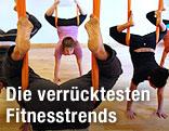 Yogateilnehmer hängen kopfüber in Stoffschaukeln