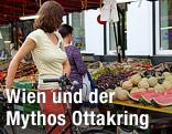 Frau mit Fahrrad steht vor Obststand am Brunnenmarkt