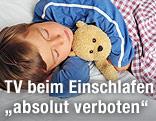 Kind mit Teddy schläft