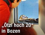 """Eine Ausstellungsbesucherin betrachtet die Gletschermumie """"Ötzi"""" durch ein Fenster"""