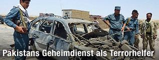 Polizisten bei zerbombten Auto in Afghanistan
