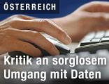 Person tippt auf einer Tastatur und bedient eine Maus