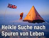 Eine Person steht mit Kapuze und Anorak vor einem Zelt in der Antarktis und neben der britischen Flagge.