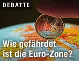 Finger hält eine Euromünze auf einen Globus