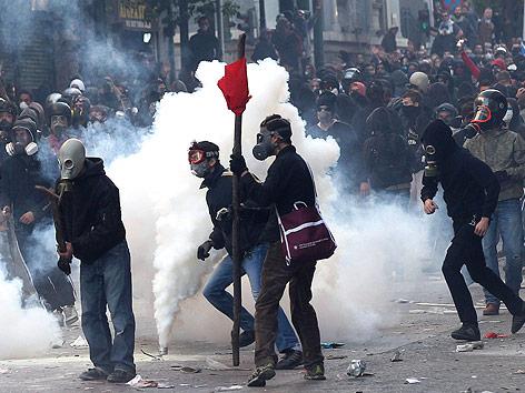Griechische Demonstranten mit Gasmasken neben einer rauchenden Tränengaskartusche
