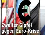 Eine Statue hält ein Euro-Zeichen vor verschiedenen Flaggen im Hintergrund