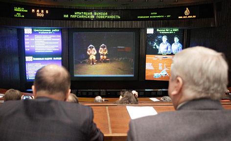 Wissenschafter beobachten in einem Kontrollraum auf Bildschirmen eine Simulation
