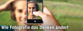 Frau wird von einem Handy fotografiert