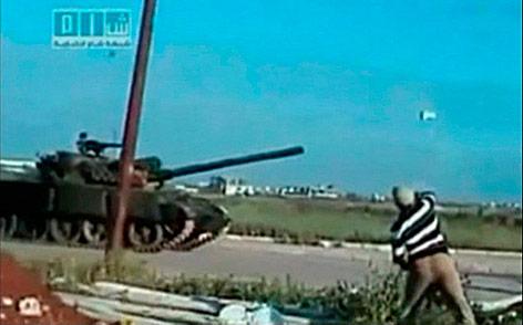 Demonstrant wirft Stein auf syrischen Panzer