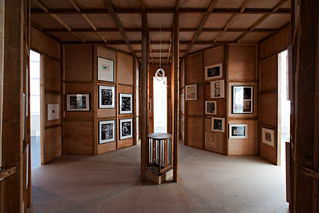 In einem Raum mit Holzvertäfelung hängen mehrere Bilder