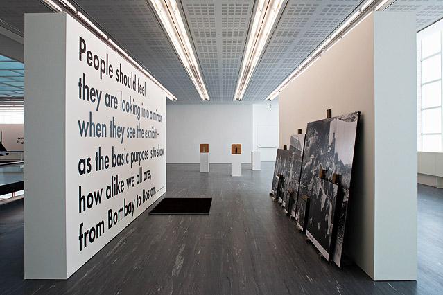 Einer Wand mit Text stehen Fotos gegenüber