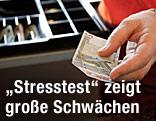 Kassierin hat einen Fünf-Euro-Schein in der Hand