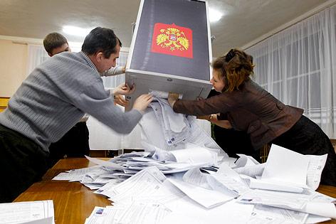 Wahlhelfer entleeren Box mit Stimmzetteln