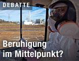 Arbeiter in Schutzanzug betrachtet Fukushima aus einem Fenster aus