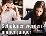 Ein junges Paar sitzt frustriert vor einem Laptop mit Rechnungen