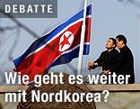 Zwei Männer hissen die nordkoreanische Flagge auf Halbmast