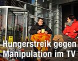TV-Journalisten Balazs Nagy Navarro und Aranka Szavuly sitzen vorm Gebäude des ungarischen Staatsfernsehens