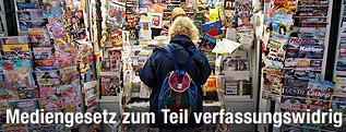 Frau steht vor einem Zeitungsstand