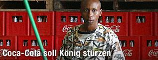 Afrikanischer Arbeiter steht vor Coca-Cola-Kisten