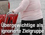 Eine übergewichtige Frau schiebt einen Einkaufswagen