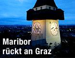 Beleuchteter Grazer Uhrturm bei Nacht