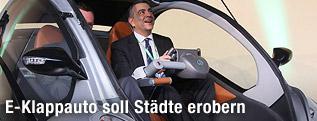 Ein Mann sitzt in einem faltbaren Elektroauto