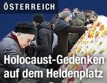 Menschen gedenken den Holocaustopfern am Heldenplatz mit Blumen