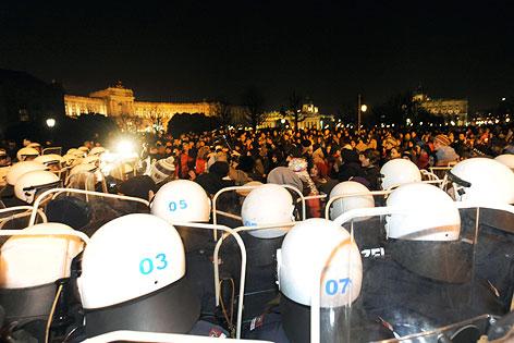 Polizisten stehen Demonstranten gegenüber, Hofburg im Hintergrund