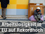 Obdachloser sitzt am Boden