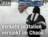 Mann kehrt verschneite Verkehrstafel ab