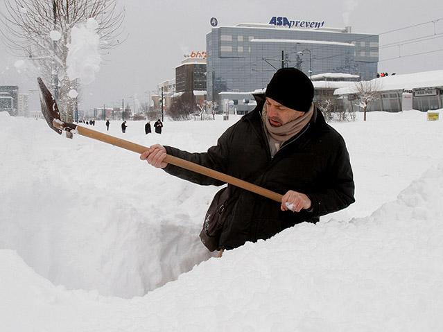 Mann beim Schneeschaufeln in Sarajevo