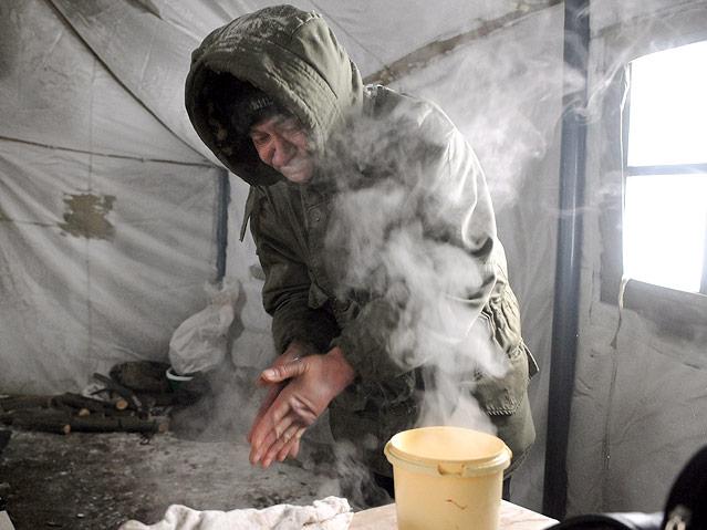 Obdachloser wärmt sich im zelt in Lviv, Ukraine
