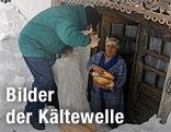 Frau erhält Brot von Helfern