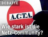 """Demonstrant hält einen Zettel mit der Aufschrift """"ACTA"""""""