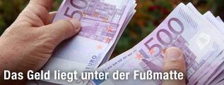 Hände mit mehreren 500-Euro-Scheinen