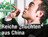 Reicher chinesischer Mann mit Zigarre in einem Club