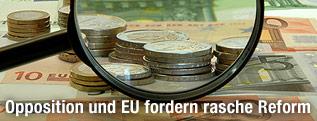 Blick durch eine Lupe auf Euro-Scheine und -Münzen